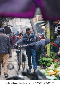 Kathmandu, Nepal - December 9, 2018: A man walking with his bike through Asan market crowd.