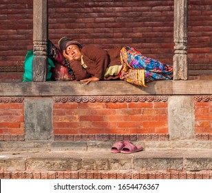 Kathmandu / Nepal - February 2016: Old poor barefoot Hindu woman in bright traditional clothes sleep in sunlight on Kathmandu street near Pashupatinath complex