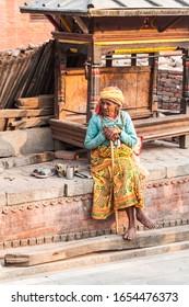 Kathmandu / Nepal - February 2016: Old poor barefoot woman in bright traditional clothes sitting on the sun on Kathmandu street near Pashupatinath complex
