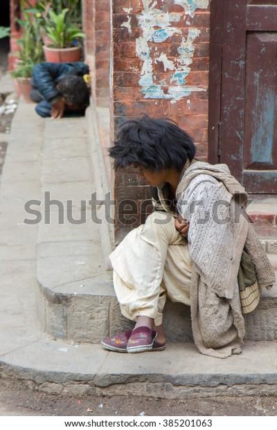 KATHMANDU, NEPAL - FEBRUARY 29, 2016: Young boy sits in the streets.