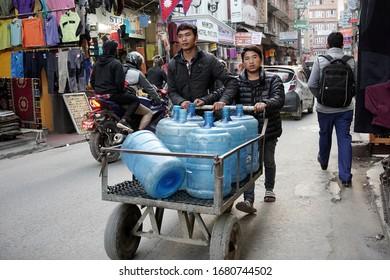 Kathmandu, Nepal - February 3, 2020: Porters push a trolley containing bottles along a busy city centre street.