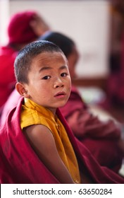 KATHMANDU, NEPAL - JANUARY 06: Little buddhist monk Dorje Tsering, 8, during puja ceremony in gelug-pa monastery on January 06, 2010 in Boudnath, Kathmandu Valley, Nepal.