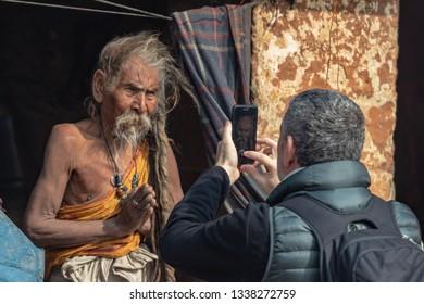 Kathmandu, Nepal- January 12, 2019: European tourist takes a picture of a Sadhus with long hair in Pashupatinath temple in Kathmandu.