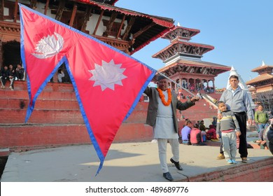 KATHMANDU, NEPAL - JANUARY 13, 2015: Nepalese man holding the Nepalese flag at Durbar Square