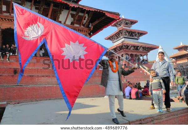 KATHMANDU, NEPAL - JANUARY 13, 2015: Nepalese man holding the Nepalese flag at Durbar Square