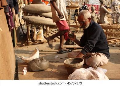 KATHMANDU, NEPAL - JANUARY 2: Preparation to Shiva Ratri Festival, man sculpts a clay bowl in street workshop, January 2, 2009 in Kathmandu, Nepal.