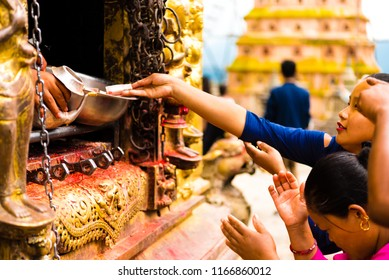 Kathmandu, Nepal - July 15, 2018 : People praying at the Monkey temple Swayambhunath Stupa complex, a UNESCO heritage site and an important place of worship for Buddhists