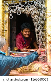 Kathmandu, Nepal - July 15, 2018 : Visitors buying traditional candles for offerings at Monkey temple Swayambhunath Stupa complex, UNESCO heritage site and an important place of worship and pilgrimage