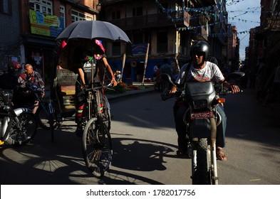 Kathmandu, Nepal - June 20, 2019: Transport traffic Man on motorbike and cycle rickshaw on narrow street in old town, Local daily life