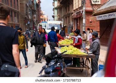 Kathmandu, Nepal - March 18, 2019: Woman and man selling fruits at Asan market in the morning.