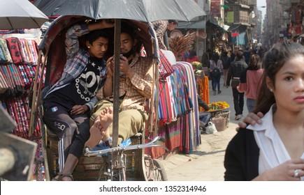 Kathmandu (Nepal) - March 18th, 2019: Thamel area. Two young boys on a rickshaws, using a smartphone