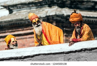 Kathmandu, Nepal - May 05 2018: Three sadhu on the terrace of Pahupatinath temple