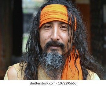 KATHMANDU, NEPAL - MAY 14, 2016:  Young Hindu Brahmin with long black curls and yellow bandana poses at Shree Pashupatinath Temple, on May 14, 2016.