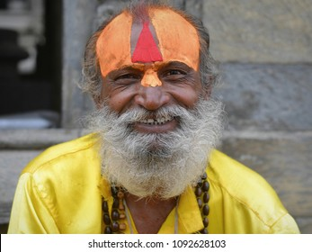 KATHMANDU, NEPAL - MAY, 14, 2016: Smiling Nepalese sadhu and yogi with fresh yellow sandalwood paste (chandanam) and red tilaka mark on his forehead poses for the camera, on May 14, 2016.