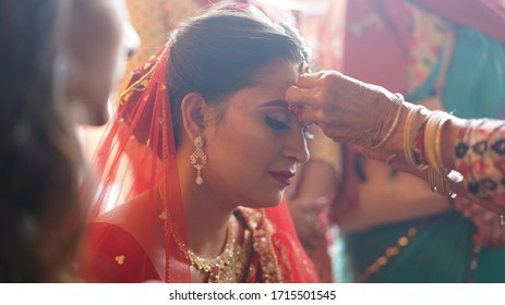 Kathmandu, Nepal - May 15, 2019: a young beautiful Nepali girl is a bride and going to marry today, her mother is blessing her with tika on her forehead
