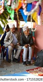 Kathmandu, Nepal - May 15, 2019: two old adult local Nepali men are sitting and watching a celebration of a wedding
