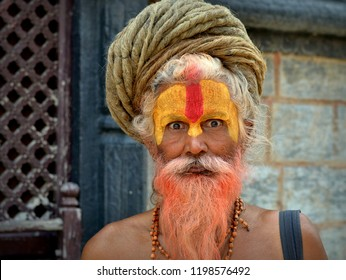 KATHMANDU, NEPAL - MAY 16, 2018: Barechested, elderly Nepali sadhu and yogi with rolled-up, turban-shaped dreadlocks and yellow sandalwood paste on his forehead poses for the camera, on May 16, 2018.