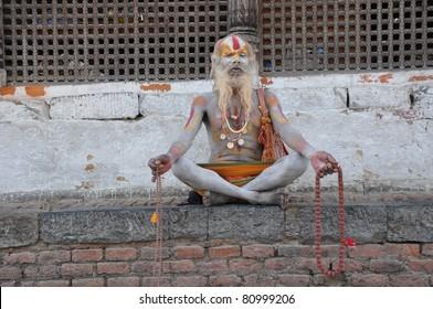KATHMANDU, NEPAL - MAY 17: Sadhu at Pashupatinath Temple at May 17, 2011 in Kathmandu, Nepal. A Hindi ascetic Sadhu sits and practicing yoga.