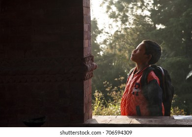 KATHMANDU, NEPAL - Nov 14, 2015 : Little nepalese student is waiting by the window. He is looking up and thinking.