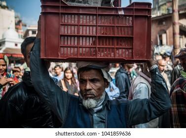 Kathmandu, Nepal - Nov 2 2014: Man carries plastic box on his head