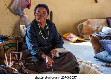 KATHMANDU, NEPAL - NOV 4: Unidentified Tibetan refugee working in a weaving house on Nov 4, 2013 in Kathmandu, Nepal. Over 20,000 Tibetans migrated to Nepal in the late 1950s and early 1960s.