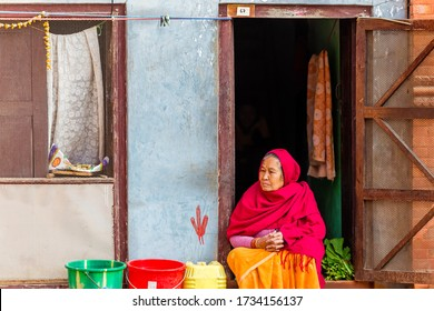 Kathmandu, Nepal - November 24, 2018 : Old Nepalese woman looking outside while sitting on the door at house in Kathmandu. Casual Lifestyle of older people.