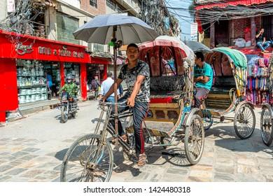 Kathmandu, Nepal - Oct 11, 2018: Drivers parking their cycle rickshaws and waiting for passengers in Kathmandu, Nepal