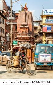 Kathmandu, Nepal - Oct 11, 2018: Man cycling on a rickshaw and traffic at the narrow street near Durbar square in Kathmandu, Nepal.