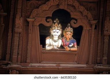 KATHMANDU, NEPAL - OCT 14, 1987 - Shiva and Parvati, Hindu gods, peering out from carved balcony,  Kathmandu,  Nepal, Asia