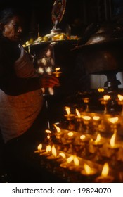 KATHMANDU NEPAL OCT 1979 - Nepali woman making offering at altar with candle lamps,Swyambudnath TempleKathmanduNepal, Asia
