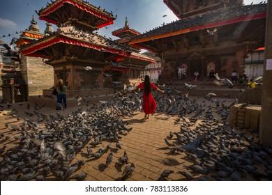 KATHMANDU, NEPAL, Oct 9, 2017. A tourist walks between thousands of pigeons in Durbar Square, Kathmandu, Nepal. Kathmandu is one of the favorite tourist destinations.