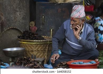 Kathmandu, Nepal - October 24, 2013: Old Nepali man selling in Kathmandu Dubar square market on October 24, 2013. His waiting customer to sell dry fish.