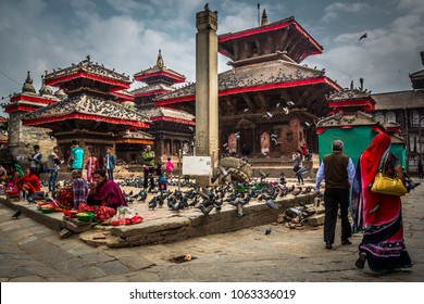 KATHMANDU, NEPAL - OCTOBER 29, 2017. Square Durbar full of people in bright apparel selling goods and pigeons on roofs of ancient temples in the center of Kathmandu, Nepal