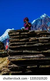 KATHMANDU, NEPAL - OCTOBER 30, 2016 ; Small girl, sitting on the rock and making Namaste salutation gesture with her hands, Manaslu trek, Himalaya mountains, Nepal. Nepalese traditional greeting.