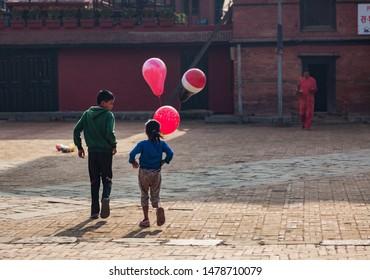 Kathmandu / Nepal - September 27 2015: Boy and girl walking in a square in Kathmandu with three pink balloons.