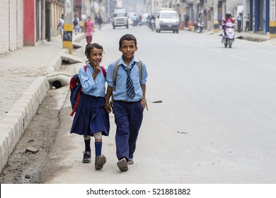 KATHMANDU, NEPAL - SEPTEMBER 29, 2016 : Young boy and girl going home from school after lessons at the local school in Kathmandu, Nepal