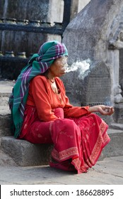 KATHMANDU, NEPAL - SEPTEMBER 29: Old, mature woman smoking medicinal herbs for relaxation on the streets of Kathmandu. On Sept. 29, 2013 in Kathmandu, Nepal