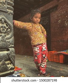 Kathmandu, Nepal / UK - February 2018: Little girl stands thinking in Patan Durbar Square, whilst leaning on a carved pole at a temple