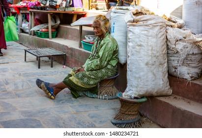 Kathmandu, Nepal-November 02,2017: poor senior women sitting on a Nepali stool on a market place