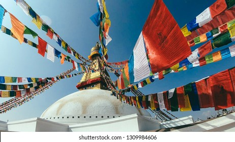 Kathmandu/Nepal - 11 11 2018: Buddhist stupa of Boudha Stupa. Prayers flags in all the colors are attached to the top of the stupa. The eyes of the Buddha watching the world. Soft colors. Bright sun