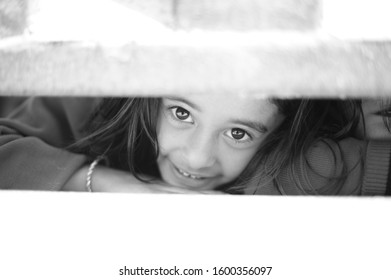 Kathmandu/Nepal- December 25, 2013 : A close up of a cute Nepali girl peeking under school's gate.