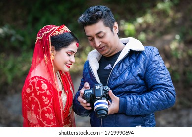 Kathmandu,Nepal - January 29,2020 : Beautiful Nepali bride watching her photos in camera with photographer in outdoor wedding photoshoot. Hindu Wedding photos