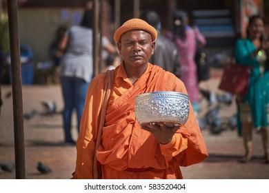 KATHMANDU/NEPAL - NOVEMBER 12, 2016: Tibetan monk in orange robe standing at the street of Kathmandu with a big bowl and begging for money