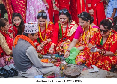 Kathmandu,Nepal - Sep 2,2019 : Nepali Women offering prayers to god according to hindu rituals with holy men during Teej Festival in Kathmandu. In Teej,women fast & pray for their husband's long life.
