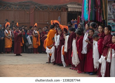 Kathmandu,Nepal-January 12, 2019:  A group of young Buddhist monks in traditional red robes wait for the master in the street.
