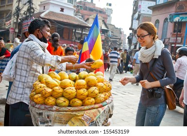 KATHMANDU,NEPAL-MAY 19:Unidentified woman buys mangoes on May 19, 2013 at Durbar sqaure in Kathmandu, Nepal. It is one of the 3 royal cities in the Kathmandu valley, a very popular spot for tourists.