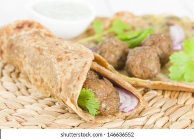 Kati Roll - Kofta kebabs and red onion pickle rolled in a paratha fried with eggs. Indian street food.
