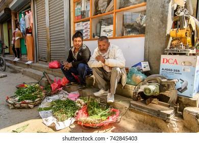 KATMANDU, NEPAL - MAR 6, 2017: Unidentified Chhetri two men sell greens. Chhetris is the most populous ethnic group of Nepal