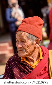 KATMANDU, NEPAL - MAR 6, 2017: Unidentified Chhetri man in red hat and colored clothes looks away. Chhetris is the most populous ethnic group of Nepal