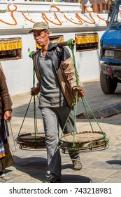 KATMANDU, NEPAL - MAR 6, 2017: Unidentified Chhetri man carries a huge scales. Chhetris is the most populous ethnic group of Nepal